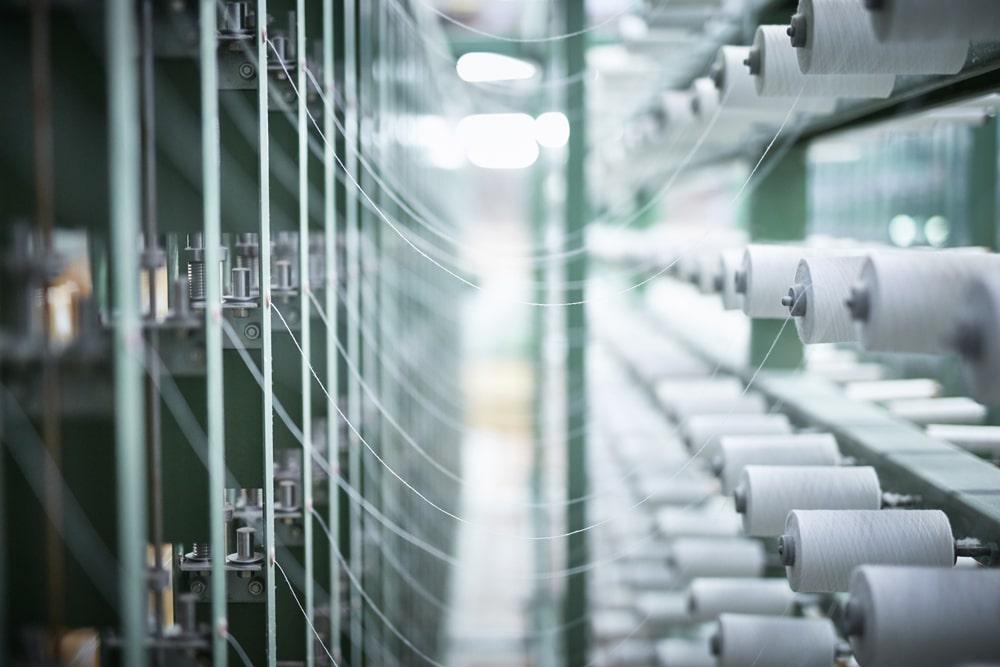 Ikeuchi's advanced looms arrange an intricate web of organic cotton thread